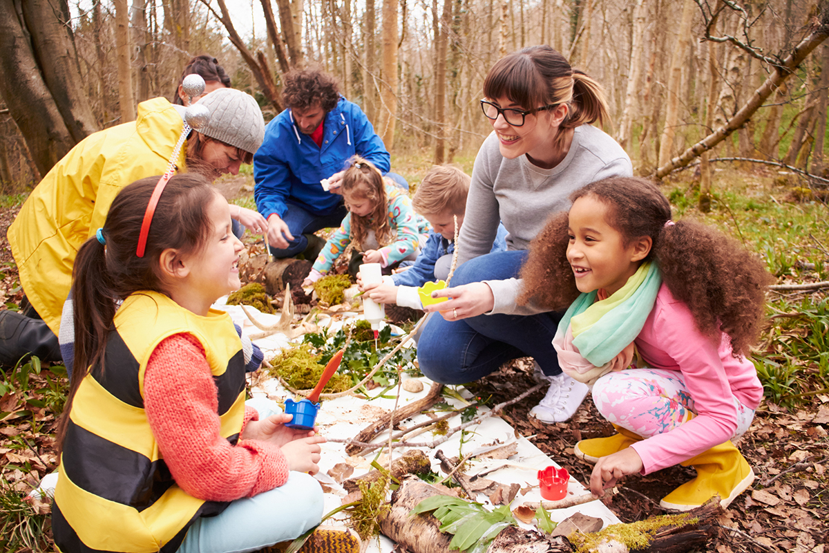 teachers and kids in an outside classroom using the outdoor environment to teach
